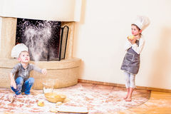 Two siblings - boy and girl - in chef`s hats near the fireplace sitting on the kitchen floor soiled with flour, playing with food stock photo