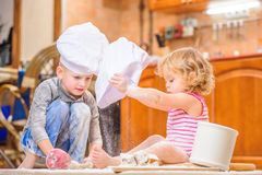 Two siblings - boy and girl - in chef`s hats sitting on the kitchen floor soiled with flour, playing with food, making mess and ha Stock Photo