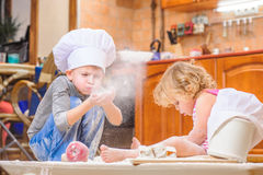 Two siblings - boy and girl - in chef`s hats sitting on the kitchen floor soiled with flour, playing with food, making mess and ha Royalty Free Stock Images