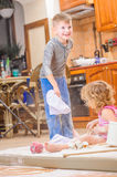 Two siblings - boy and girl - in chef`s hats sitting on the kitchen floor soiled with flour, playing with food, making mess and ha Royalty Free Stock Image