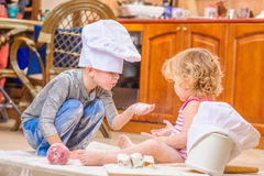 Two siblings - boy and girl - in chef`s hats sitting on the kitchen floor soiled with flour, playing with food, making mess and ha Royalty Free Stock Photos
