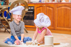 Two siblings - boy and girl - in chef`s hats sitting on the kitchen floor soiled with flour, playing with food, making mess and ha Royalty Free Stock Photography