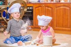 Two siblings - boy and girl - in chef`s hats sitting on the kitchen floor soiled with flour, playing with food, making mess and ha Stock Photos