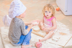 Two siblings - boy and girl - in chef`s hats sitting on the kitchen floor soiled with flour, playing with food, making mess and ha Stock Image