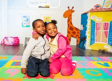 Two siblings boy, girl in play room hug and smile royalty free stock images