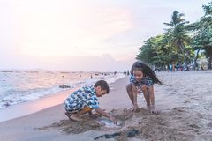 Two siblings children playing with wave and sand in Pattaya Beach Thailand stock photo