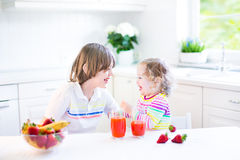 Two siblings having fruit for breakfast drinking juice Stock Photos