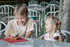 Two siblings having fun eating their sweet Italian gelato ice cream. Two siblings are having fun eating their sweet Italian gelato ice cream Royalty Free Stock Photo