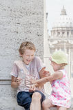Two siblings having fun with water from plastic bottle in hot summer day Stock Image