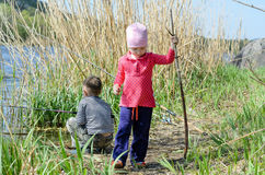 Two Siblings Holding Fishing Rods at the Riverside Stock Photo