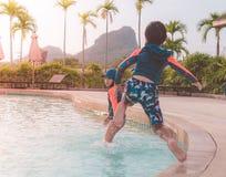 Two siblings in jumping down in Water Aqua park pool stock photos