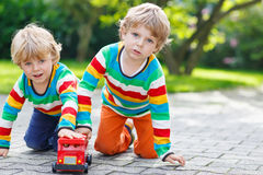 Two siblings, kid boys playing with red school bus Stock Photography