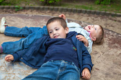 Two siblings lying on the carousel Stock Photography