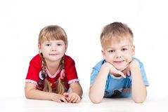Two siblings lying Isolated on white background Royalty Free Stock Images