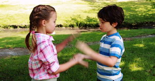 Two siblings playing clapping game in park