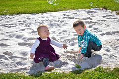 Two siblings playing in the sand Royalty Free Stock Images
