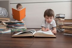 Two siblings read big books. royalty free stock image