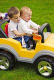 Two siblings in toy car Stock Images