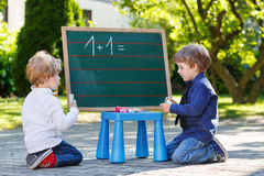 Two siblinig boys at blackboard practicing mathematics Royalty Free Stock Images