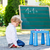 Two siblinig boys at blackboard practicing mathematics Royalty Free Stock Photography