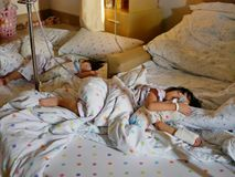 Two sick Asian baby girls, siblings, were together admitted and staying in a hospital. Selective focus of two sick Asian baby girls, siblings, were together stock images