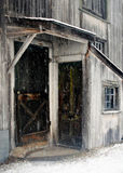 Two side door and multiple windows to old, dirty white New England barn in a December snow storm. Grimy snowing rusty screen doors snowing Royalty Free Stock Image