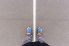 Two sides on asphalt ground, feet and shoes on floor Royalty Free Stock Photos