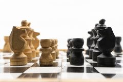 Two sides of black and white chess pieces, which are made of wood, are facing each other. There is a white background for placing. Posts stock image