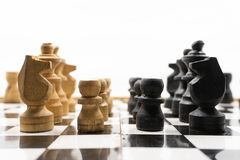 Two sides of black and white chess pieces, which are made of wood, are facing each other. There is a white background for placing. Posts royalty free stock photography