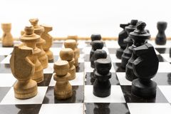 Two sides of black and white chess pieces, which are made of wood, are facing each other. There is a white background for placing. Posts royalty free stock photos