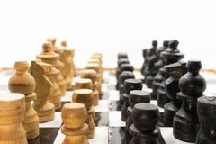 Two sides of black and white chess pieces, which are made of wood, are facing each other. There is a white background for placing. Posts stock photo
