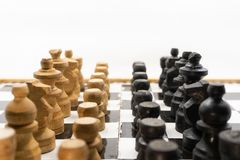 Two sides of black and white chess pieces, which are made of wood, are facing each other. There is a white background for placing. Posts stock photography