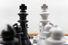 Two sides of chess pieces with black kings and white kings and their pawns facing each other. There is a white background for stock photo
