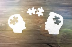 Two silhouette of a head from a paper, puzzles. On a background of a wooden table Stock Images