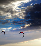 Two silhouette of power kites at sunset sky Royalty Free Stock Photos