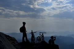 Cyclists on high mountainside. Two silhouetted cyclists with bikes on mountainside looking over distance peaks stock photos