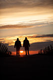 Two silhouetted seniors walking in sunset Royalty Free Stock Image