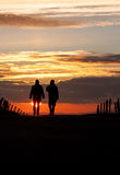 Two silhouetted seniors walking in sunset Stock Photography