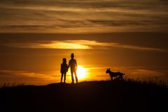 Two silhouettes of a child at sunset background stock photos