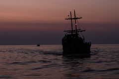 Two silhouettes of ships sailing on the sea royalty free stock images