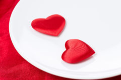 Two silk heart on a plate on red background, selective focus Royalty Free Stock Image