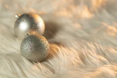 Two silver Christmas balls. On a white fur royalty free stock photography