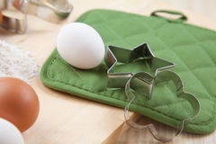 Two silver cookie mold with white egg on wooden table Royalty Free Stock Image