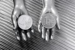 Two silver euro coins in futuristic robot hands Stock Photos
