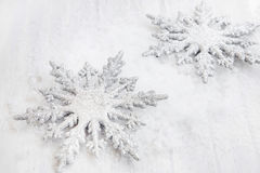 Two Silver Glittered Snowflakes Ornaments in the Snow. Two Silver Glittered Christmas Snowflakes Ornaments in the Snow Stock Photo