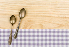 Two silver spoons on a purple checkered table cloth. On a wooden background Royalty Free Stock Photos