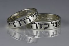 Two silver wedding rings, Song of Songs, Hebrew. Two silver wedding rings with the words of Song of Songs 6:3 in Hebrew, `I am my beloved`s and my beloved is royalty free stock photography