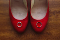 Two silver wedding rings on stylish red bride`s shoes, rustic wo Royalty Free Stock Photography