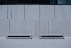 Two Similar Benches Against White Building Wall Stock Photo
