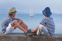 Two similar brother sitting on waterfront,. Talking , watching ship Stock Photography